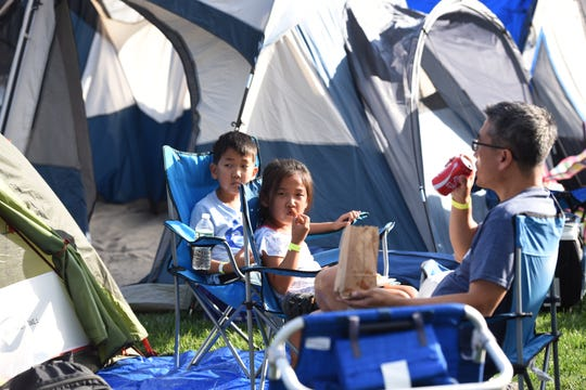 The Emerson Police Dept Community  hosted  its annual free open house/movie night together with a free overnight family camp out for Emerson residents.Joseph 8, Olivia 6 and their father Pau Kim have a snack infront of their tent.
