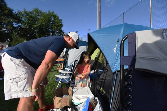 The Emerson Police Dept Community  hosted its annual open house/movie night together with a free overnight family camp out for Emerson residents. Rod Giella and his 5-year-old daughter, Jacqueline, inspect their tent and provisions.
