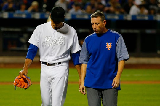 Aug 24, 2019; New York City, NY, USA; New York Mets relief pitcher Edwin Diaz (left) leaves the field with trainer Brian Chicklo after sustaining an apparent injury against the Atlanta Braves during the ninth inning of an MLB Players' Weekend game at Citi Field.