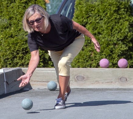 Lorie Galbraith, who has been playing at the court for ten years, rolls out a ball during a Bocce Ball tournament at Victor's Italian Restaurant in Spring Garden Township.