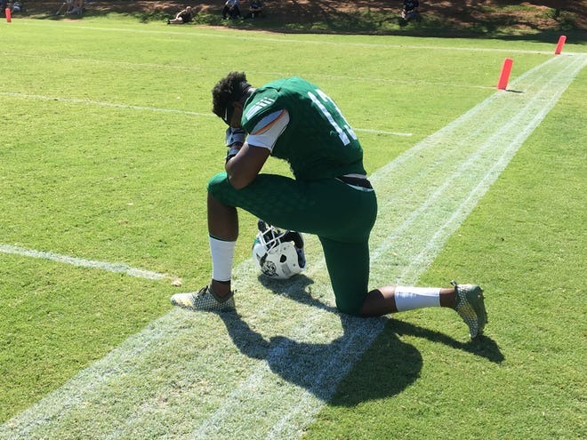 Brandon Morris takes a knee in prayer before Shasta College faced Redwoods in a scrimmage on Saturday, Aug. 24, 2019.