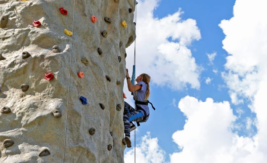 A climber scales a wall during the House of Faith festival on Saturday, Aug. 24, 2019.