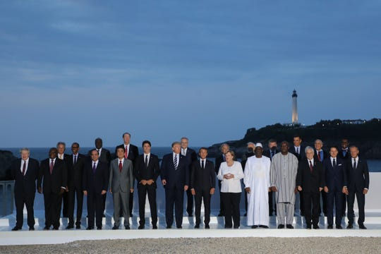 "President Donald Trump poses with other G7 leaders and guests for a ""family photo"" during the group's summit in Biarritz, France. The summit, in its second day, has been marred by behind-the-scenes discord."