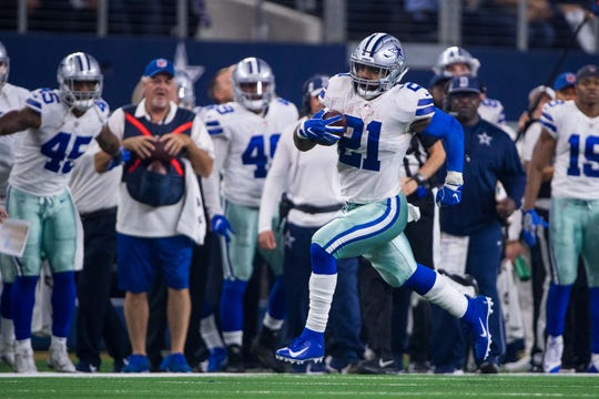 Ezekiel Elliott runs down the sidelines during the NFC Wild Card game against the Seattle Seahawks.