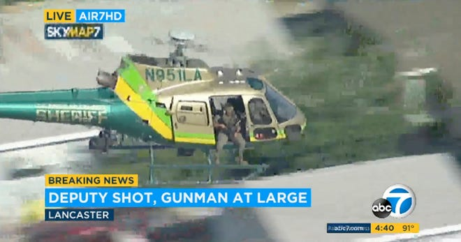 This photo taken from video provided by KABC-TV shows a sheriff's department helicopter with a sniper in an open door searching for a reported gunman at large in Lancaster, Calif., on Aug. 21, 2019. The sheriff's office now says the deputy who said he was shot lied about the whole thing.