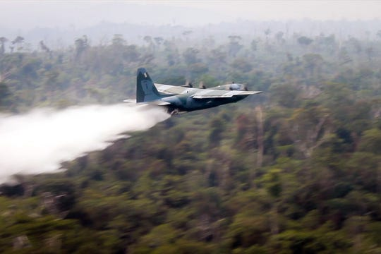A C-130 Hercules from Brazil's Air Force drops water on a fire in the state of Rondonia, Brazil, on Aug. 25 2019.  Around 44,000 soldiers will be deployed in the vast Amazon region to fight forest fires in the states of Rondonia, Roraima, Tocantins, Para, Acre and Mato Grosso.