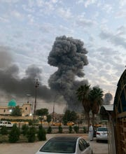 In this Monday, Aug. 12, 2019 file photo, plumes of smoke rise after an explosion at a military base southwest of Baghdad, Iraq. Israel was responsible for the bombing of an Iranian weapons depot in Iraq last month, U.S. officials have confirmed, an attack that would mark a significant escalation in Israel's long campaign against Iranian military entrenchment in the region.