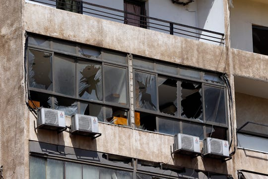 Broken windows are seen on the 11-floor building that houses the media office in a stronghold of the Lebanese Hezbollah group in a southern suburb of Beirut, Lebanon, Sunday, Aug. 25, 2019.
