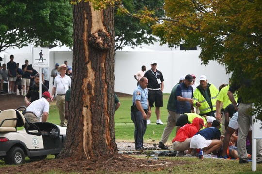 Fans are assisted by medical personnel after a lightning strike during the third round of the Tour Championship.