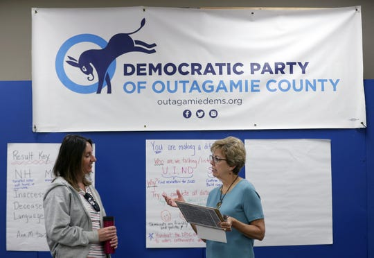 Lee Snodgrass, chairwoman of the Outagamie County Democratic Party, talks with Political Outreach Chairwoman Ann Muenster about how to teach volunteers to have good conversation with voters during a canvassing session on Aug. 24 in Appleton.