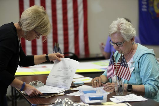 Denise Fenton, left, of Appleton, checks in as a canvasser with Sharon Olski of Kimberly during a canvassing session with the Outagamie County Democratic Party on Aug. 24 in Appleton.