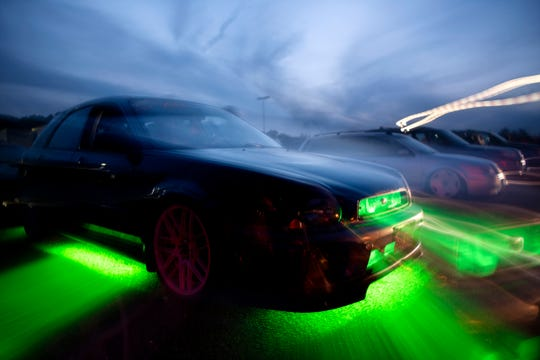 Green lights glow beneath a car in a lot owned by Prairie Farms on Sunday, Aug. 25, 2019 in Battle Creek, Mich. A car club called AutoMODIFIED must find a new space to legally race their vehicles as the lot undergoes new management.