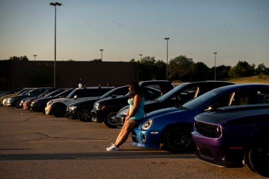 Vanessa Reed sits on her husband's car before AutoMODIFIED's Food and Friends event on Thursday, Aug. 22, 2019 at Barnes and Noble in Battle Creek, Mich. The car club, AutoMODIFIED, meets on Thursday evenings to parade their vehicles and eat food together.