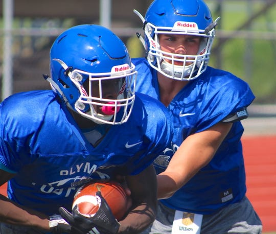 Olympic quarterback Zeke Gillick hands off to running back Malcolm DeWalt during practice on Saturday.