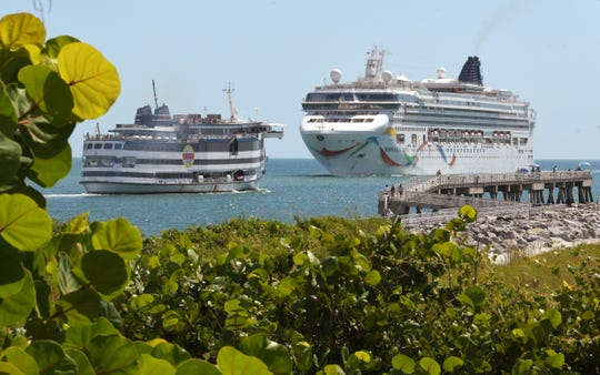Norwegian Cruise Line ship Norwegian Dawn, on right, arrives at Port Canaveral, while a Victory Casino Cruise ship leaves.