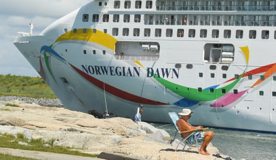 Richard Lutz relaxes in the sun at Jetty Park, as the Norwegian Cruise Line ship Norwegian Dawn arrives at Port Canaveral.