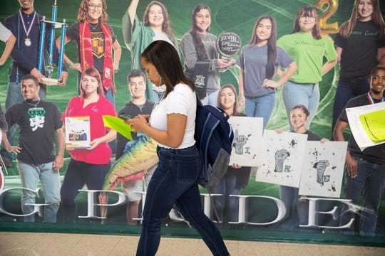 A student walk past a giant photograph at King High School on the first day of school on Monday, August 26, 2019.
