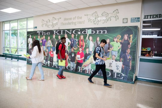 Students walk past a giant photograph at King High School on the first day of school on Monday, August 26, 2019.