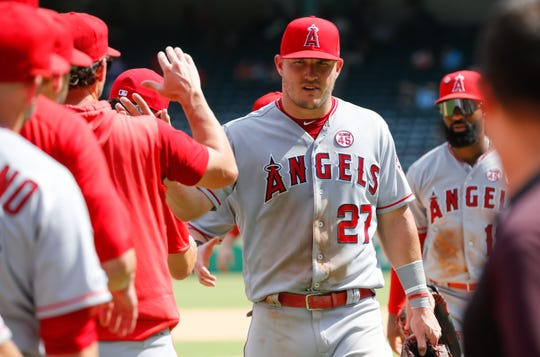 Los Angeles Angels center fielder Mike Trout (27) high fives teammates following a recent game against the Texas Rangers at Globe Life Park. Mandatory Credit: Ray Carlin-USA TODAY Sports