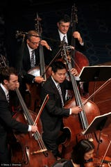 Cincinnati Symphony Orchestra bassist Owen Lee, front right, performs with the All-Star Orchestra during the filming of a PBS TV special in New York in 2012.
