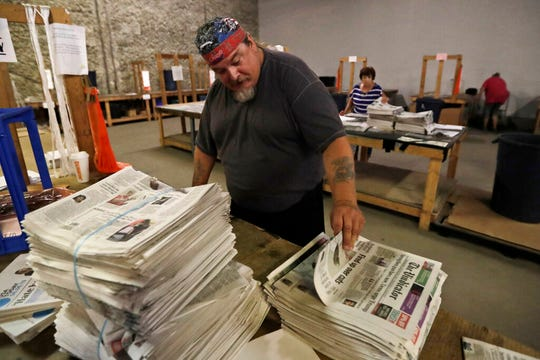 In this Tuesday, Aug. 6, 2019, photo, Paul Reitz sorts newspapers for delivery at the distribution center in Liberty Township near Youngstown, Ohio. The Youngstown paper announced in June it would cease publication Saturday, Aug. 31, because of financial struggles, but the paper will be printed by the Tribune Chronicle, which has bought The Vindicator name, subscriber list and website from owners of the Youngstown publication. (AP Photo/Tony Dejak)