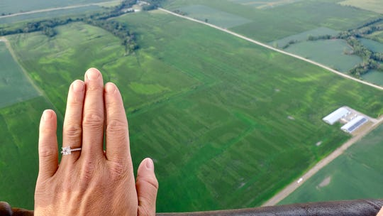 Shelby Chapman holds out her hand to show off her new engagement ring on August 2, 2019, above the message her fiance, Aaron Adam, planted for her.