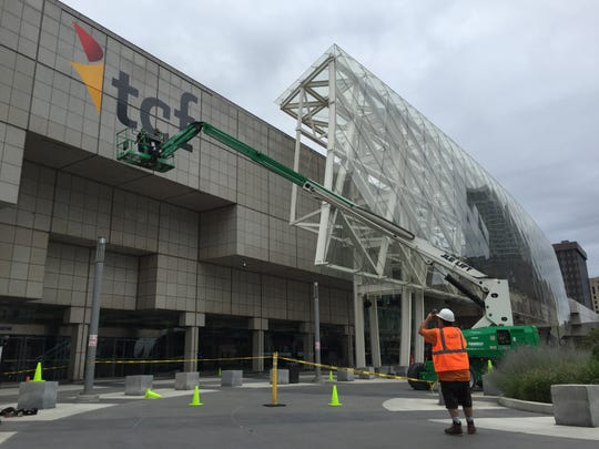 Bob Brown, a carpenter with Convention Show Services, photographs the installation TCF Center name on the front of Cobo Center on Monday, August 26, 2019 in Detroit.