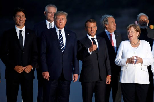 Canadian Prime Minister Justin Trudeau, left, President Donald Trump, French President Emmanuel Macron and German Chancellor Angela Merkel pose during the G7 family photo Sunday.