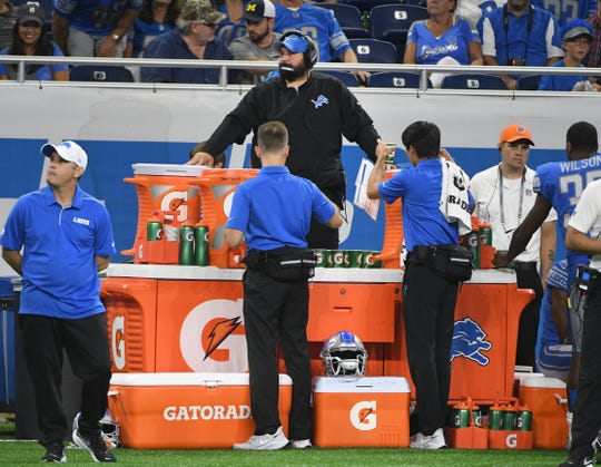 Lions head coach Matt Patricia watches from the sidelines behind a wall of Gatorade containers for safety during his team's preseason game against the New England Patriots on Aug. 8 at Ford Field in Detroit.
