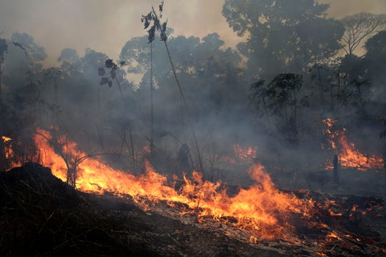 A fire burns along the road to Jacunda National Forest in the Vila Nova Samuel region which is part of Brazil's Amazon, Monday.