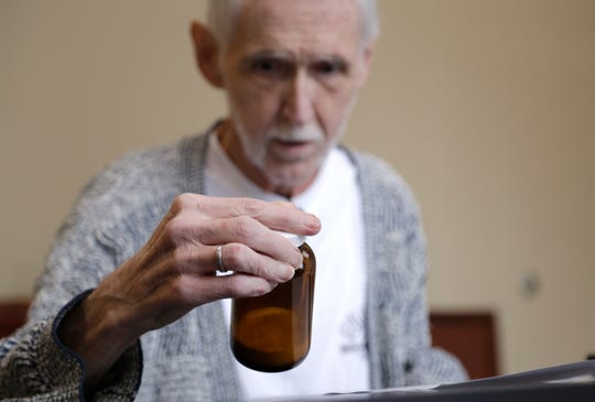 On May 3, Robert Fuller looks at the vial containing the drugs that will end his life a week later as he is counseled about it at a compounding pharmacy in Seattle.