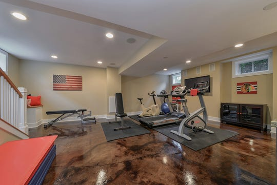 This below-grade workout space features acid-stained concrete, which is easy to clean. Rubber mats placed on the floor provide cushion and nonslip protection.