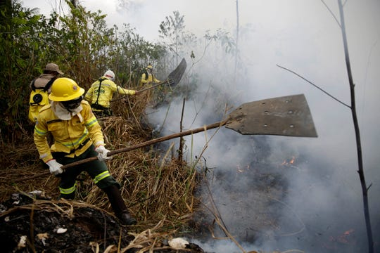 Firefighters work to put out fires along the road to Jacunda National Forest in the Vila Nova Samuel region which is part of Brazil's Amazon, Monday.
