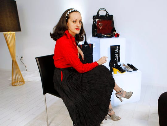 This Aug. 25, 2010 file photo shows designer Isabel Toledo posing with her shoes and handbags designed for Payless ShoeSource in Miami Beach, Fla. Toledo, the Cuban-American fashion designer with an avant-garde flair who created former first lady Michelle Obama's standout lemongrass-colored sheath dress and matching overcoat for her husband's 2009 inauguration, has died. She was 59.