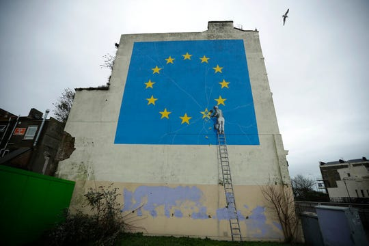 In this file photo dated Monday, Jan. 7, 2019, a mural by street artist Banksy, depicting a star being chiselled from the European flag, stands in Dover, south east England.