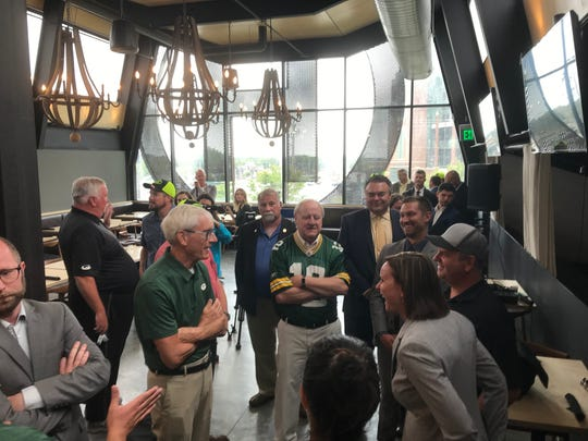 Gov. Tony Evers, left, and state Sen. Dave Hansen, center, in the Packers jersey, talk with Greater Green Bay Convention and Visitors Bureau staff about the need for a new Green Bay area visitors center at Hinterland Brewery Monday.