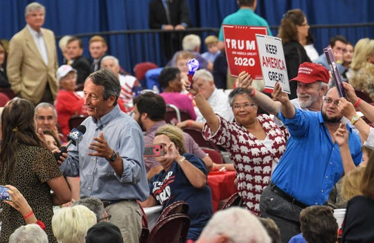 U.S. President Donald Trump supporters holds signs behind former State Gov. Mark Sanford as he is interviewed during the Faith and Freedom Barbecue at the Civic Center of Anderson Monday. The annual fundraiser in Anderson is for U.S. Rep. Jeff Duncan from Laurens, with around 3,000 supporters at the event considered South Carolina's largest annual gathering of conservatives.