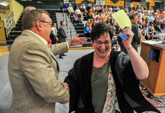 Stacey Hansen, an elementary general music teacher for the Great Falls Public Schools, shakes the hand of school board member Gordon Johnson after winning a prize at the conclusion of Monday's convocation kicking off the 2019-2020 school year.