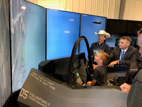 Joel Robison, 6, checks out the screen Monday before takeoff as his father, Charles, left and Jeff Cunningham of Lockheed Martin look on.