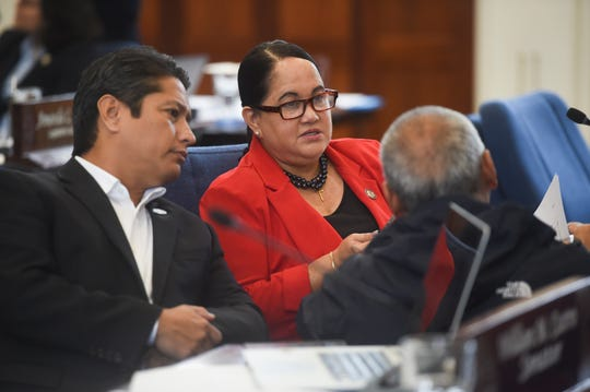 Speaker Tina Muña Barnes and Sen. Wil Castro, left, speak with Bureau of Budget and Management Research Director Lester Carlton during a session recess at the Guam Congress Building in Hagåtña, Aug. 26, 2019.