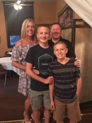 Kim Sims with her husband Jason and sons, Caden (middle) and Cooper (front).