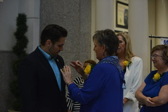 A member of the Madison Area Democratic Women pins a yellow rose to Jackson Mayor Scott Conger's suit at the announcement of a new scholarship honoring suffragette Sue Shelton White in Jackson City Hall on Aug. 26, 2019.