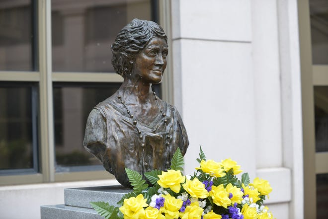 A wreath of yellow and purple flowers adorns the bust of suffragette Sue Shelton White outside Jackson City Hall on Aug. 26, 2019, the 99th anniversary of the adoption of the 19th amendment.