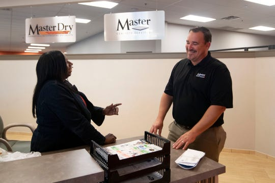 Master Services' Josh Smith chats with Office Support Specialist Cathy Benn on Aug. 26, 2019.