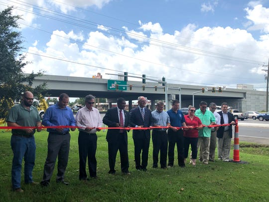Gov. John Bel Edwards and others cut a ribbon at a ceremony celebrating the Albertson Parkway widening project's completion on Aug. 26, 2019.