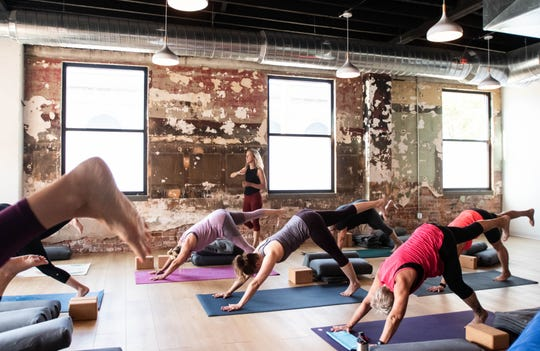 Misty Belous of Peoples Yoga in REO Town works with students Monday, Aug. 19, 2019, during a morning class.