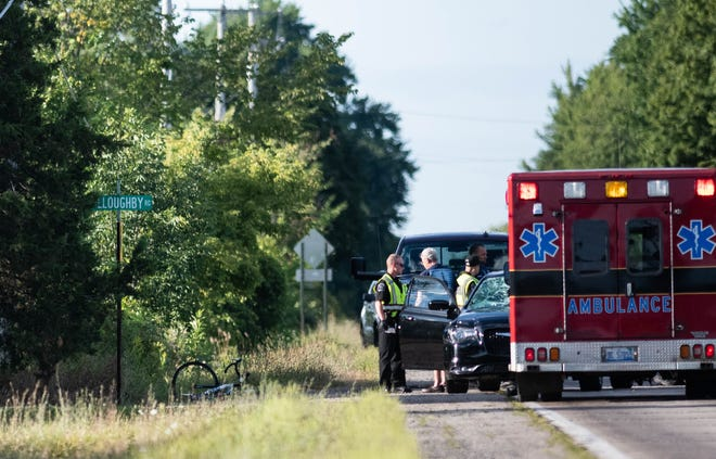 First responders work at the scene of a crash involving a bicycle and vehicle near the intersection of Okemos and Willoughby roads in Alaiedon Township Friday, Aug. 23, 2019.
