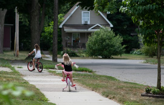 Nikki Heddens' two young nieces ride their bicycles in front of their home on Carey Street in Lansing,, Tuesday, Aug. 20, 2019  Heddens says the rental is rat infested, and she can't afford to move.