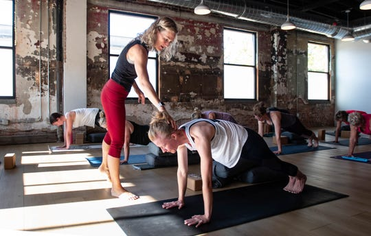 Misty Belous of Peoples Yoga in REO Town adjusts a student's posture Monday, Aug. 19, 2019, during a morning yoga class.