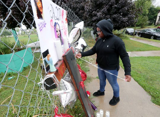 """Renee Williams, the cousin of Quanita """"Tay"""" Jackson, who was fatally shot Sunday near Moody Park, places balloons on a makeshift memorial at the scene of the shooting near North 22nd and West Burleigh street in Milwaukee on Monday."""